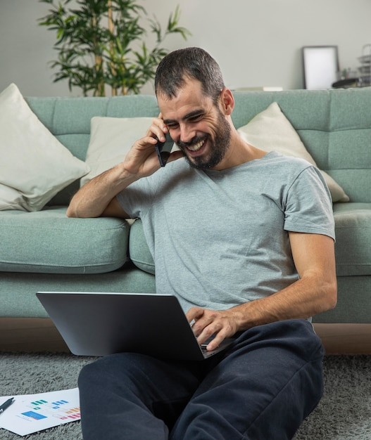 Homem sorridente falando ao telefone em casa enquanto trabalha no laptop Foto gratuita