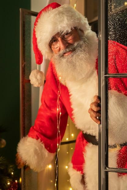Homem sorridente fantasiado de papai noel entrando em casa pela janela Foto gratuita