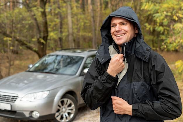 Homem sorridente, fechando sua jaqueta de inverno Foto gratuita