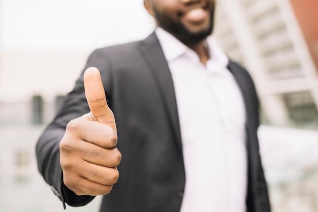 Homem sorridente gesticulando polegar para cima Foto gratuita