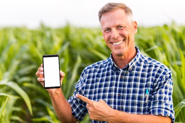 Homem sorridente indicando no mock-up do telefone Foto gratuita