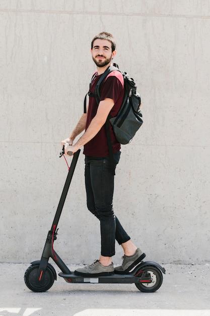 Homem sorridente, montando um e-scooter na rua Foto gratuita