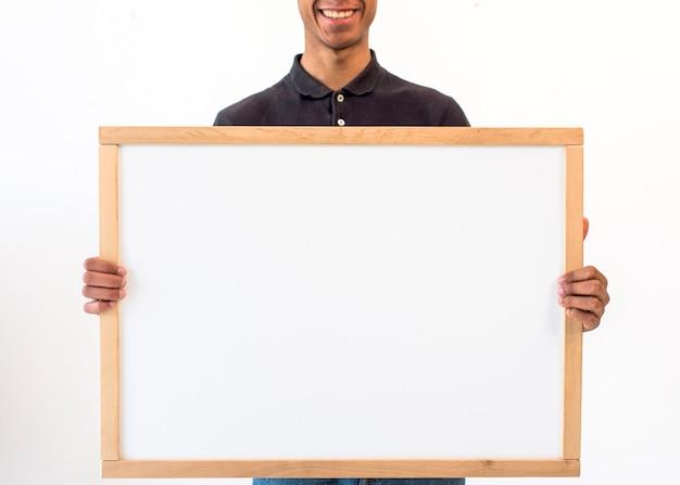 Homem sorridente, mostrando a placa branca vazia em branco Foto gratuita