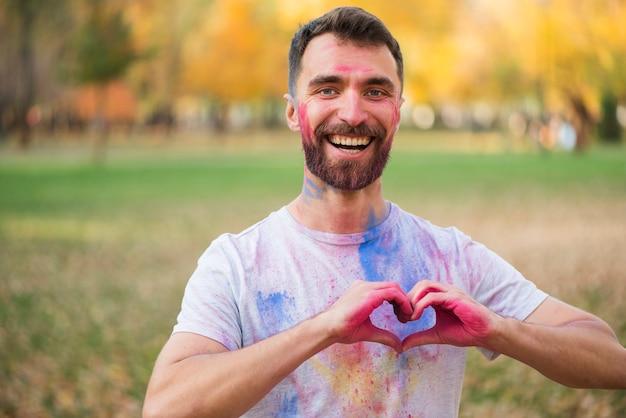 Homem sorridente, mostrando sinal de amor com as mãos pintadas Foto gratuita