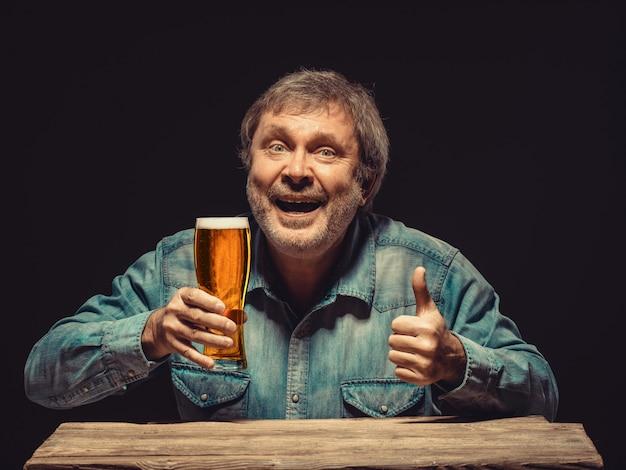 Homem sorridente na camisa jeans com copo de cerveja Foto gratuita