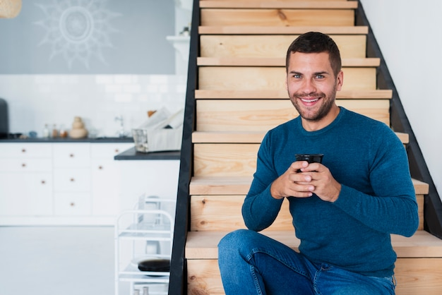 Homem sorridente, olhando para a câmera e segurando uma xícara de café Foto gratuita