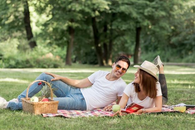 Homem sorridente, olhando para a namorada no piquenique Foto gratuita