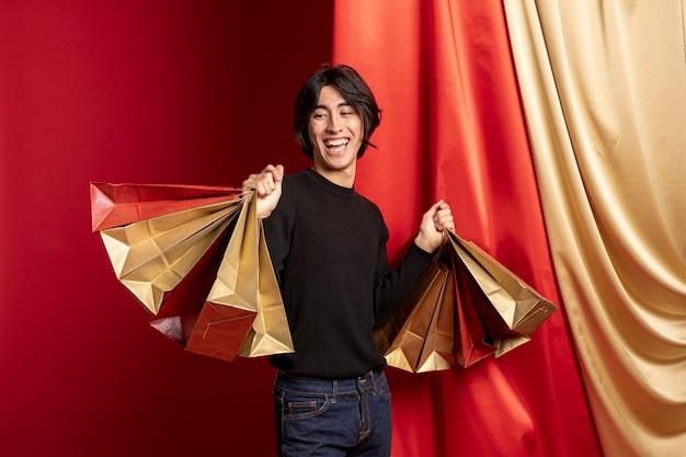 Homem sorridente posando com sacolas de compras para o ano novo chinês Foto gratuita