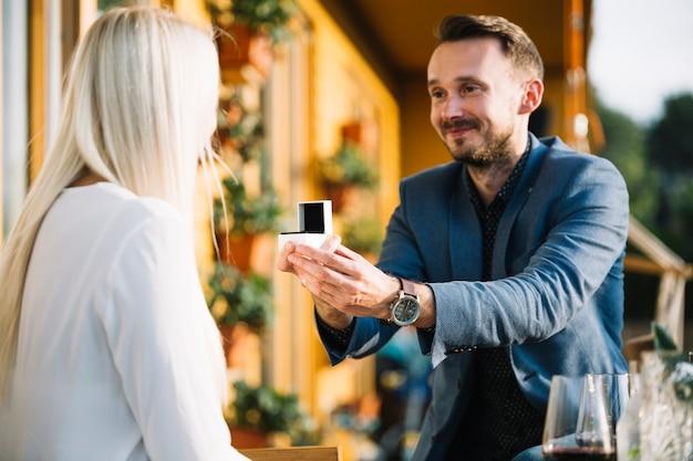 Homem sorridente, propondo a namorada dando anel de noivado Foto gratuita
