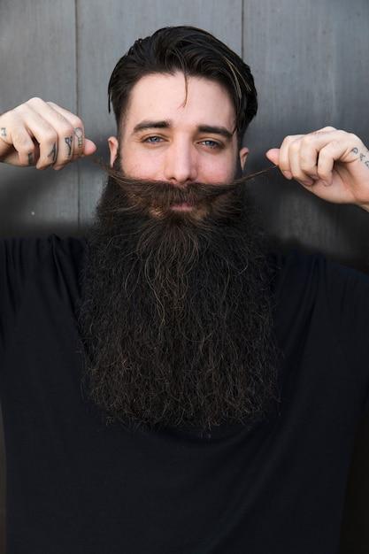 Homem sorridente, puxando, seu, bigode Foto gratuita