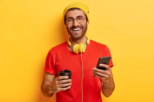 Homem sorridente satisfeito perde tempo nas redes sociais, navega na internet no celular, bebe café na xícara para viagem, tem expressão alegre e despreocupada Foto gratuita