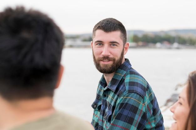 Homem sorridente se divertindo com seus amigos ao ar livre Foto gratuita
