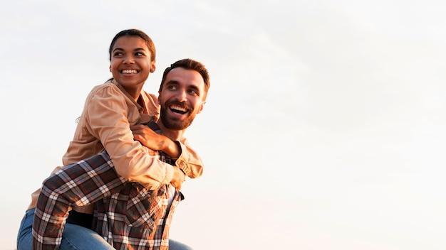 Homem sorridente segurando a namorada nas costas com espaço de cópia Foto gratuita