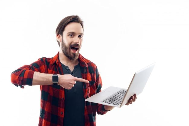Homem sorridente, segurando, laptop, e, apontar, aquilo Foto Premium