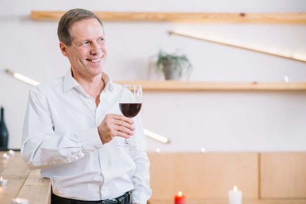 Homem sorridente, segurando, um, vidro vinho Foto gratuita