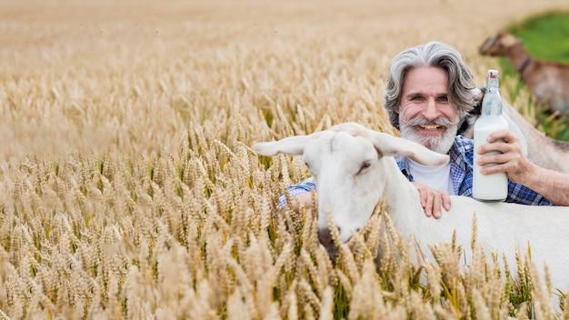 Homem sorridente segurando uma garrafa de leite de cabra Foto gratuita
