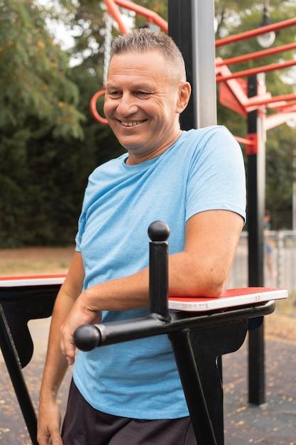 Homem sorridente sênior fazendo exercícios ao ar livre Foto gratuita