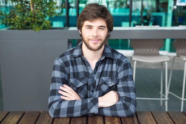 Homem sorridente, sentado à mesa de café de rua com os braços cruzados Foto gratuita