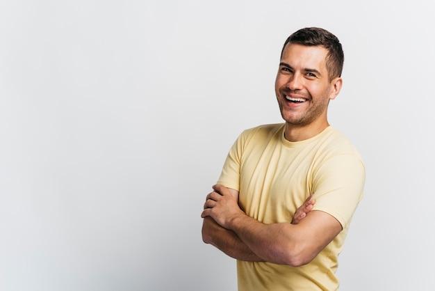Homem sorridente, tendo os braços cruzados com espaço de cópia Foto gratuita