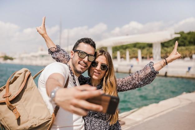 Homem sorridente tomando selfie no celular com a namorada gesticulando Foto gratuita