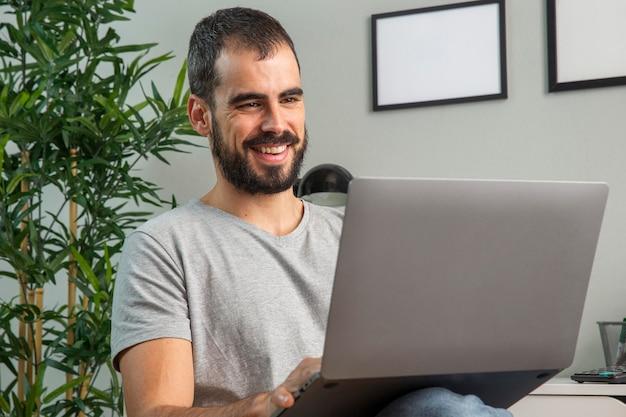 Homem sorridente trabalhando em casa em um laptop Foto gratuita