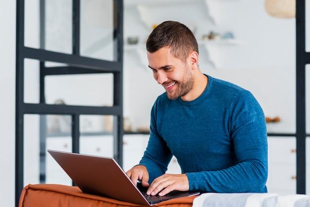 Homem sorridente trabalhando no laptop em casa Foto gratuita