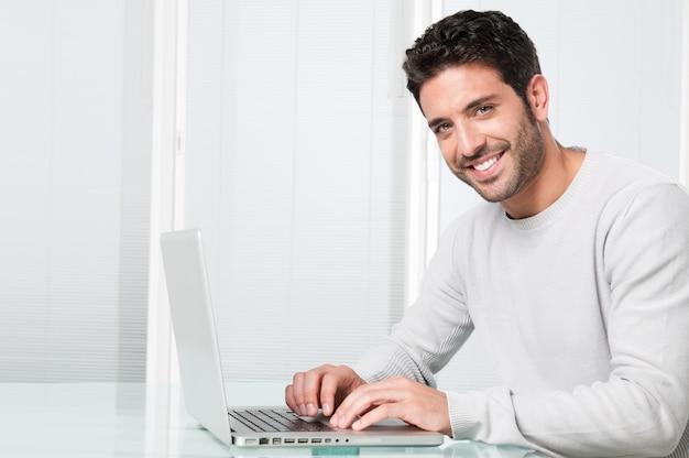 Homem sorridente trabalhando no laptop Foto Premium