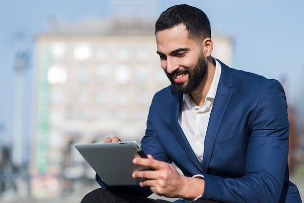 Homem sorridente trabalhando no tablet Foto gratuita