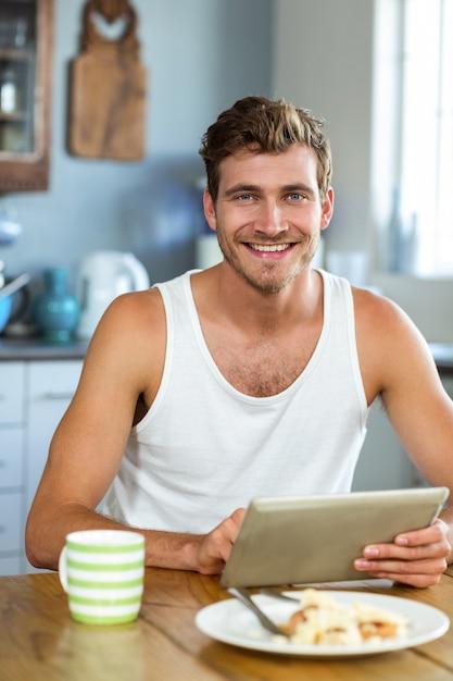 Homem sorridente usando o tablet pc na mesa de café da manhã Foto Premium