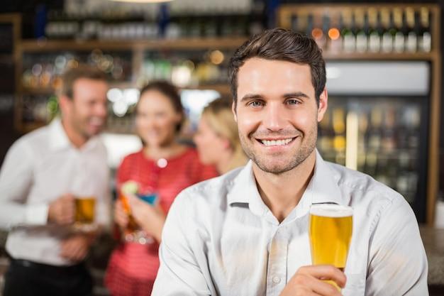 Homem sorrindo para a câmera segurando uma cerveja Foto Premium