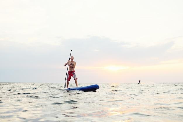 Homem, sup, tábua, contra, bonito, pôr do sol, mar Foto Premium
