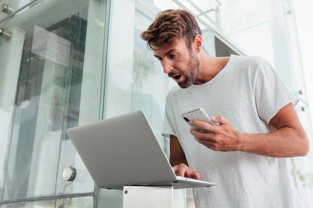 Homem surpreendido com dispositivos portáteis Foto gratuita
