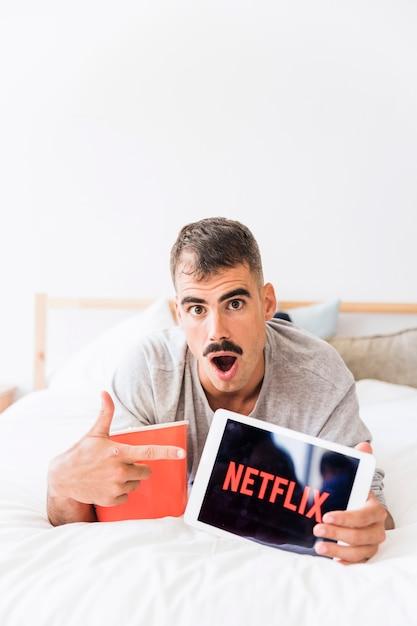 Homem surpreendido com pipoca recomendando site netflix Foto gratuita