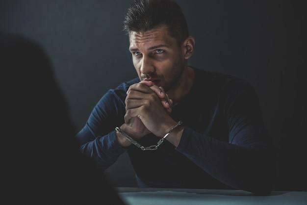 Homem suspeito ou criminoso com algemas na sala de interrogatório Foto Premium