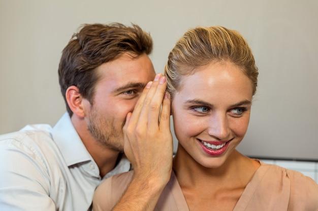 Homem sussurrando para colega no escritório Foto Premium