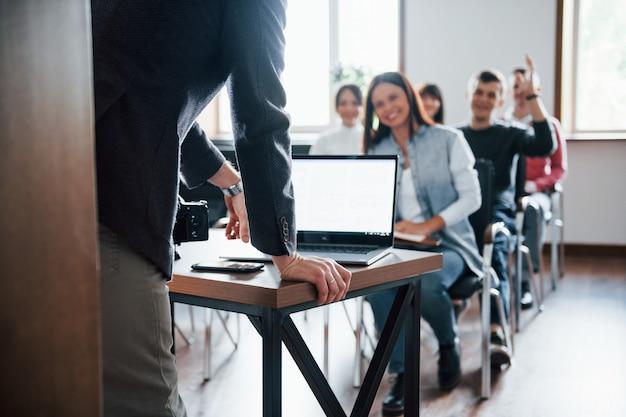 Homem tem uma pergunta. mão levantada. grupo de pessoas em conferência de negócios em sala de aula moderna durante o dia Foto gratuita