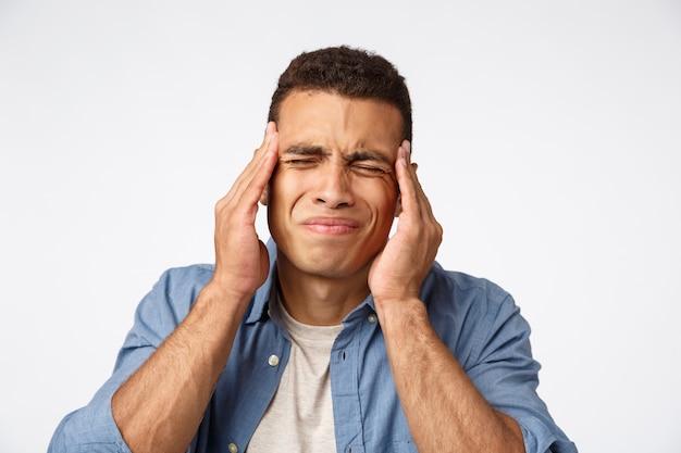 Homem tendo enorme ressaca após a festa de ano novo, franzindo a testa, fazendo uma careta incomodado Foto Premium