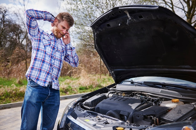 Homem tendo um problema com o carro Foto gratuita