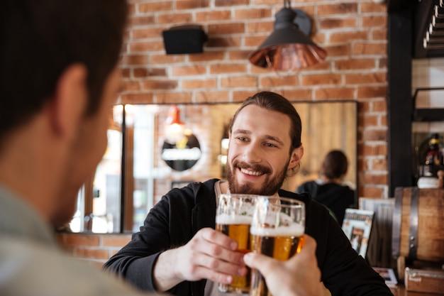 Homem tilintar de copos com amigo no bar Foto gratuita