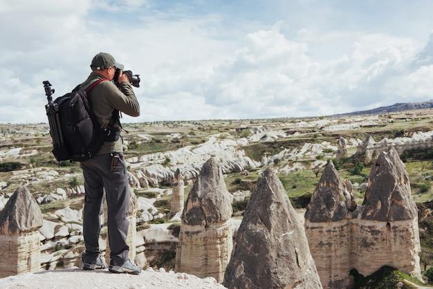 Homem tira fotos do vale amor montanhas de altitude. cappad Foto Premium