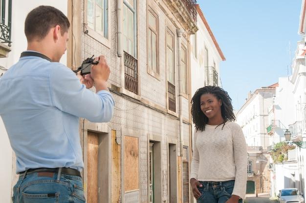 Homem tirando foto de mulher negra feliz ao ar livre Foto gratuita