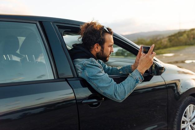 Homem tirando foto no telefone em viagem Foto gratuita