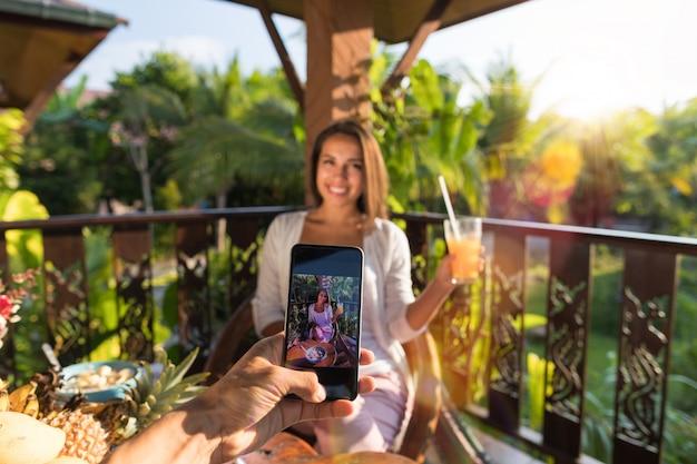 Homem tirar foto de mulher com suco no celular casal de telefone inteligente Foto Premium