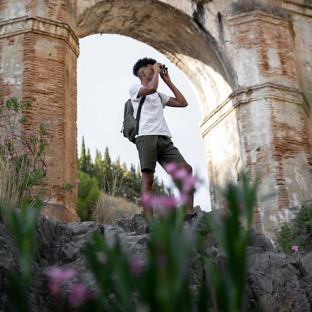 Homem tiro completo com binóculo Foto gratuita