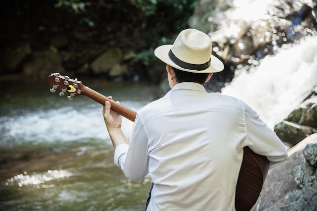 Homem toca guitarra perto da cachoeira Foto gratuita