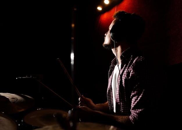 Homem tocando bateria no escuro Foto gratuita