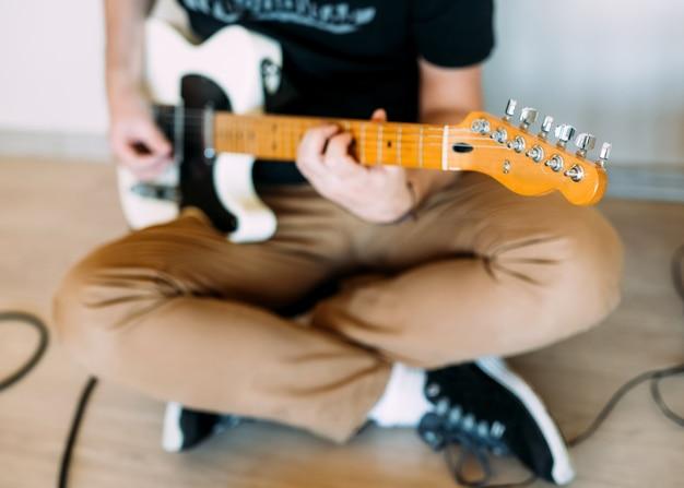 Homem tocando guitarra elétrica em casa, close-up Foto Premium