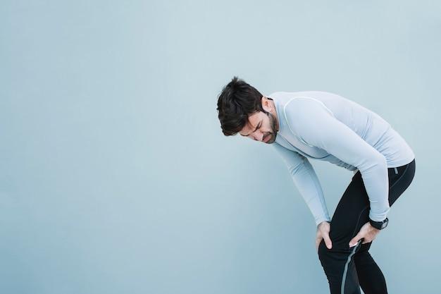 Homem tocando joelho machucado Foto Premium
