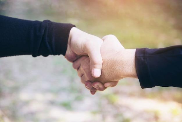 Homem tocando / segurando a mão juntos para o conceito de trabalho de compromisso de sucesso Foto gratuita