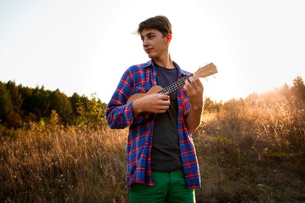 Homem tocando ukulele e olhando para longe Foto gratuita